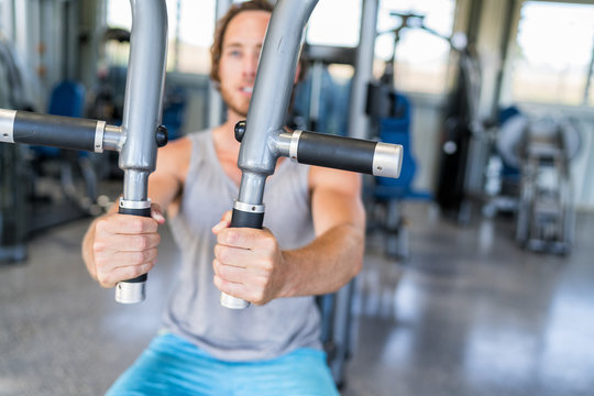 Gym machine closeup on male hands. Male athlete training chest muscles on fitness equipment pec deck fly working out strength alone indoors. Man holding handles of fitness machine at gym center.