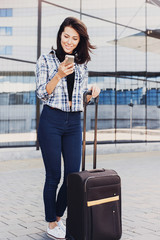 Young woman standing with luggage suitcase and using smart phone, vacations, travel and active lifestyle concept