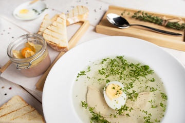 Hot bouillon with toasts and pate top view. Served plate of broth with egg and crusty bread with foie gras. French cuisine, restaurant menu, luxury food ,healthy dinner concept