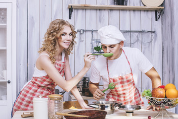 Man and woman young and beautiful couple in the kitchen home coo