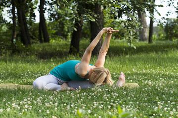 young girl practices yoga on the grass