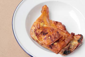 Grilled chicken leg in white dish on wooden background