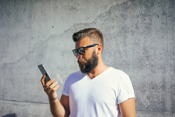 Summer sunny day, a young bearded man in sunglasses and a white t-shirt, standing outside and looking at the screen of the smartphone that is in his hand. In the background wall with concrete texture.