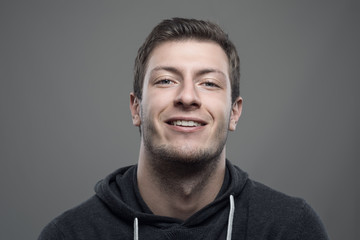 Moody portrait of proud young man smiling at camera with head leaned back