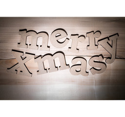 "The greeting message ""merry Xmas"" composed volumetric letters on wooden background."