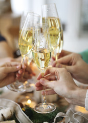 Group of friends toasting with champagne while having Christmas