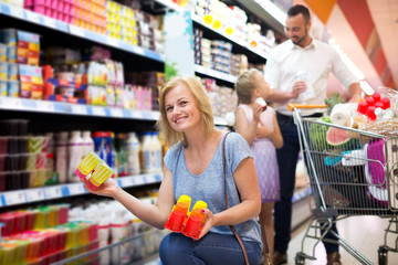 Smiling woman holding package with yogurt