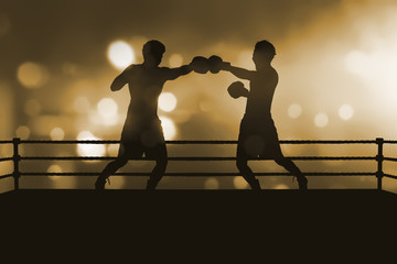 Silhouette of two professional asian boxer fight in the boxing match
