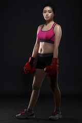 Beautiful asian woman boxer wearing red gloves