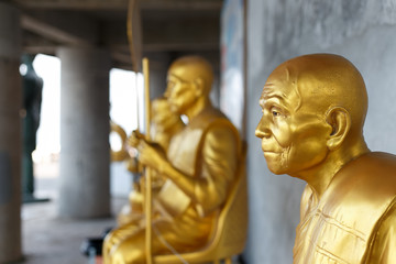 Traditional Buddhist gold statue monk in Thailand temple/ Thailand