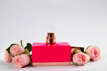 Perfume bottle with flowers on light background