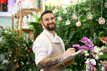 Handsome florist with notebook and pen in greenhouse