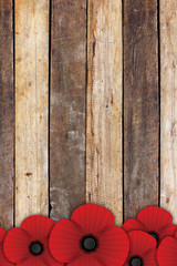 red paper poppy flower on old wooden table background. empty space for text