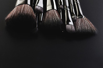 Makeup brushes set on a black background horizontal, space for t