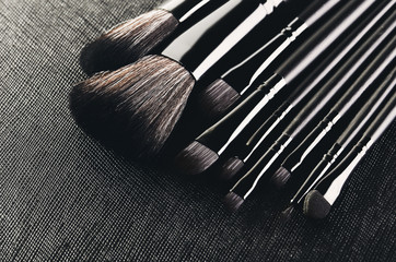 Makeup brushes set close-up on a textured black background diago