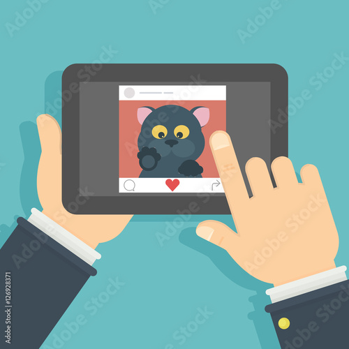 Cat on the screen  Hand holding tablet with funny black cat