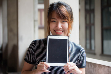 Portrait of thai adult beautiful girl using her tablet.