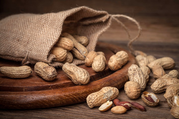 Dried peanuts in wooden bowl.