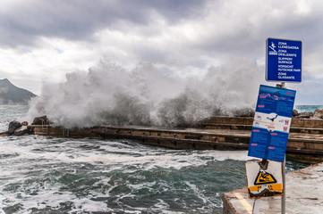 Brandung mit Schutzmauer und Warnschilder auf Mallorca