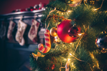 Wall Murals Christmas Beautiful decorated Christmas tree with baubles and garland decorated gingerbread, on the new-year background with fireplace and socks. The idea for postcards. Soft focus. Shallow DOF
