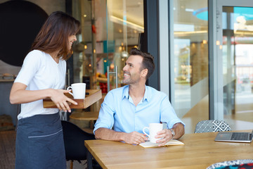Waitress serving  coffee at coffee shop to client