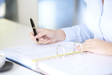 Fill the form. Close-up shot of a businesswoman using fountain pen while sitting at desk and fill the form.
