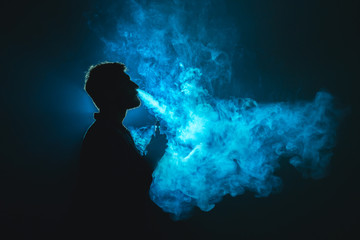 The man smoke a cigarette against the background of the blue light