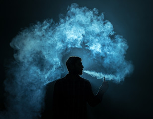 The man smoke a electronic cigarette against the background of the bright light