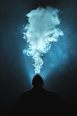 The man smoke a cigarette against the background of the bright light