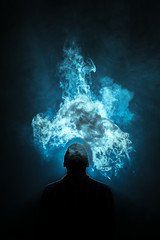 The man smoke a electronic cigarette on the dark background
