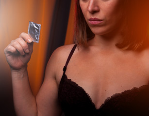 Cropped shot of woman holding condom in hand
