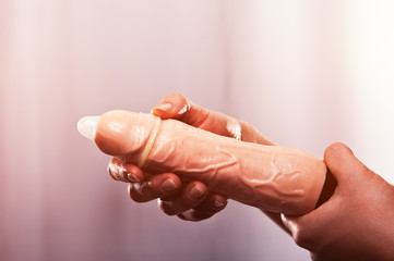 Female hand holding vibrator with condom, sex toy
