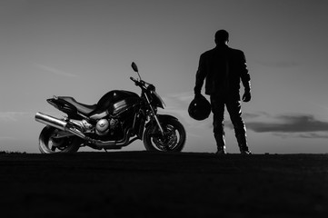 Motorcyclist standing next to bike with helmet