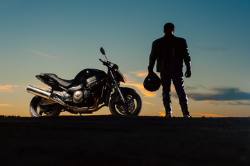 Silhouette of man in leather outfit with motorbike