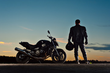Male biker in leather outfit standing next to bike