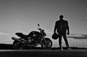 Silhouette of male biker standing next to bike