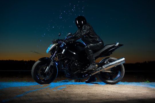 Motorbiker in helmet sitting on bike