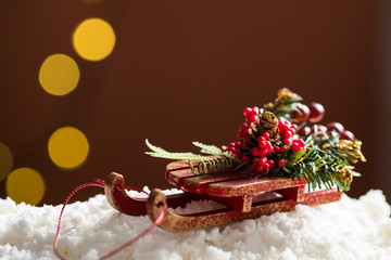 Decorative sleigh with roan-tree and christmas tree branches, driving on snow, in the background the beautiful bokech balls.