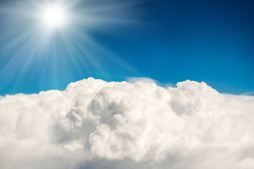 Shining sun on blue sky with white clouds