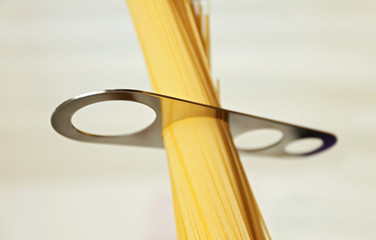 Spaghetti with measuring stick on light background