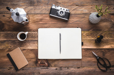 Artist, hipster, photographer wooden rustic table with black notebook, camera, coffee maker and cup of espresso. Flat lay. View from above, copy space.