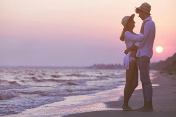 Young happy couple on sunset seashore
