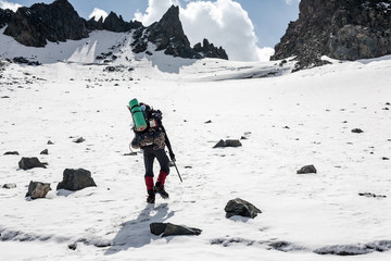 Hiker moving on land full of ice and snow at Tien Shan mountains