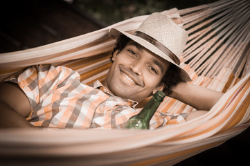 Man Relaxing and drinking a beer In Hammock
