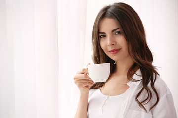 Beautiful woman with cup of aromatic coffee standing near window