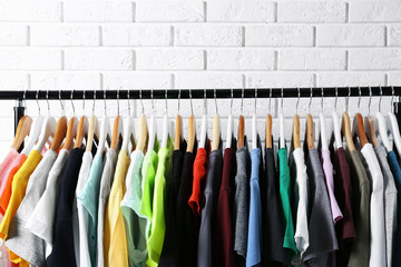 Colorful t-shirts on hangers against brick wall