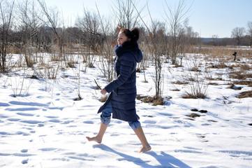 pretty girl barefoot walking on snow