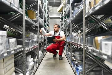 Mitarbeiter in einem Warenlager zwischen den Regalen