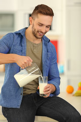 Young man pouring fresh milk into glass at kitchen