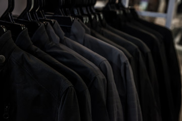 Black shirt hanging on a rack in the store. Fashion and garment